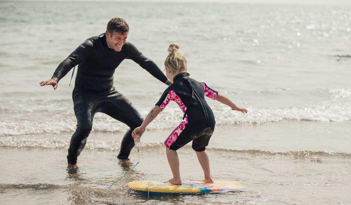 Dad Teaching a Little Girl how to Surf on holiday in North Devon