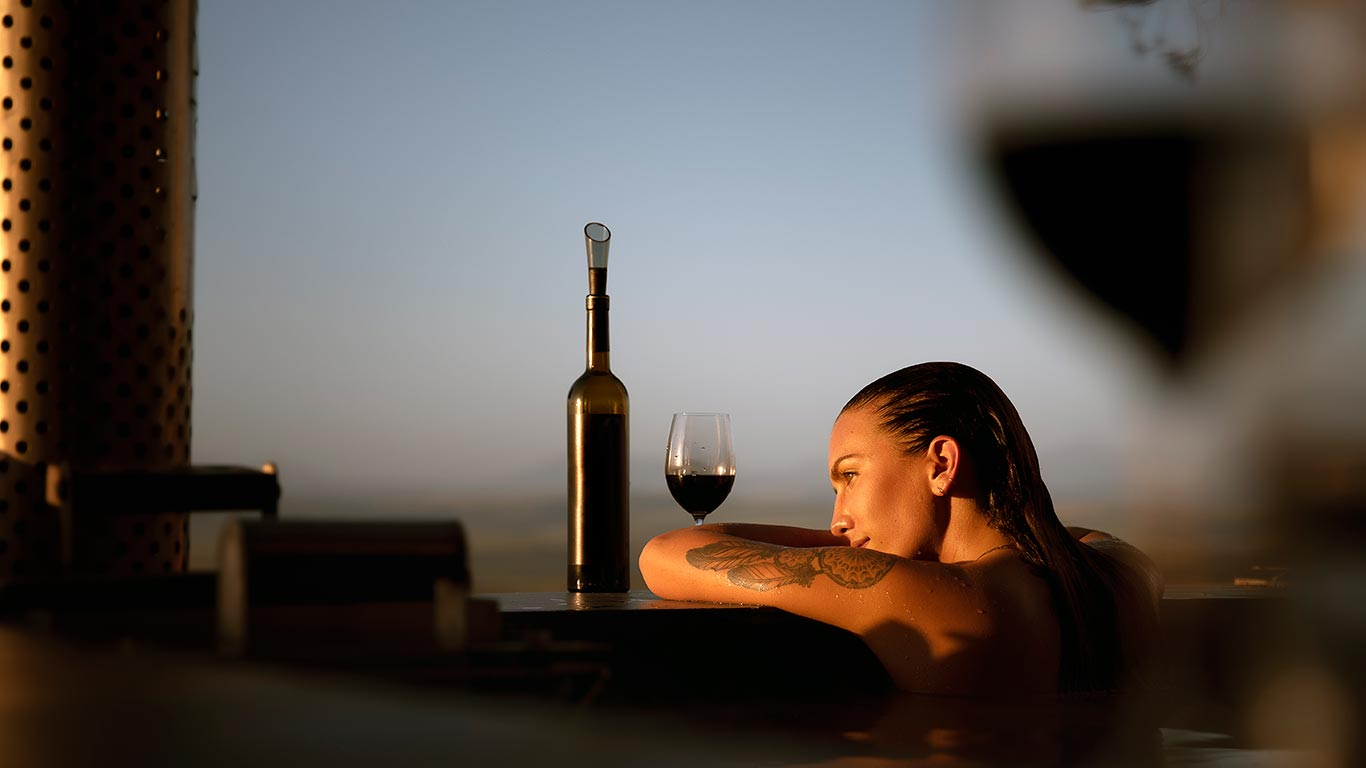 Woman looking at sunset in North Devon from hot tub in Holiday Cottage
