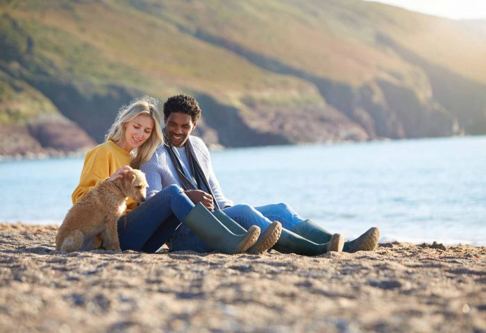 Couple with dog on beach whilst on Autumn holiday in North Devon
