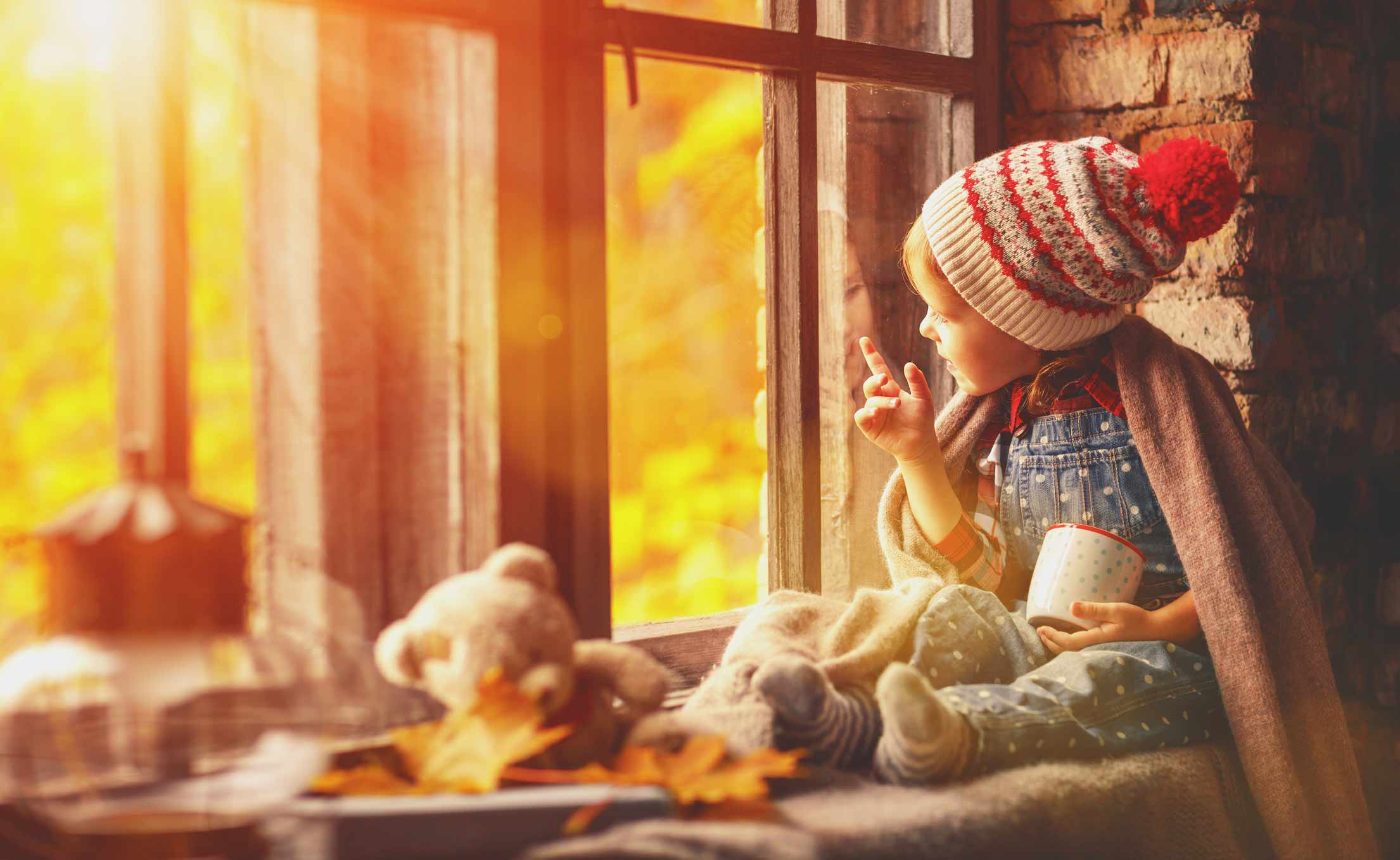 Girl looking out of window at autumn leaves whilst on holiday in Devon